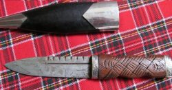 Beautiful Scottish Sgian Dubh traditional form hard wood handle silver mounts cap with Highland theme castings Handle is simple carved blade is serrated edge groove
